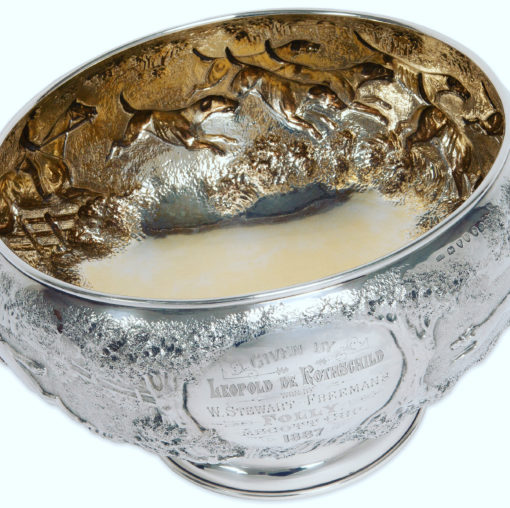 """A magnificent and rare large Silver Victorian Rose Bowl with a chased fox hunting scene, depicting three and a half couple of hounds pursuing a fox in open landscape with the huntsman jumping a post and rail fence, a gentleman mounted with top hat and a house, most likely Ascott house. Makers: James Berkeley Hennel, London 1884. Includes Company Trade Mark. Weight 55 Ounces. Gilt Interior. IMPORTANT Rothschild connection. The Inscription is set between two oak trees and reads, """"Given by Leopold De Rothschild, Won By W. Stewart-Freeman's Folly, Ascott Cup 1887"""""""