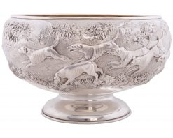 A magnificent large Silver Victorian Rose Bowl with a chased fox hunting scene, depicting three and a half couple of hounds pursuing a fox in open landscape with the huntsman jumping a post and rail fence, a gentleman mounted with top hat and a house, most likely Ascott house. Makers: James Berkeley Hennel, London 1884. Includes Company Trade Mark. Weight 55 Ounces. Gilt Interior.